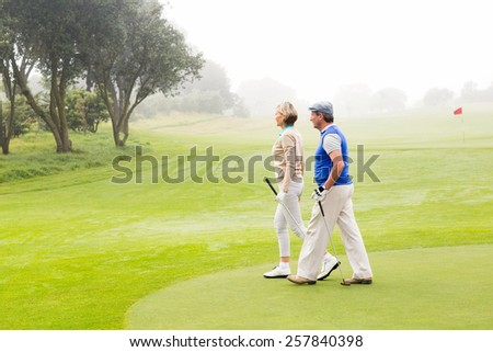 Golfing couple walking on the putting green on a foggy day at the golf course - stock photo