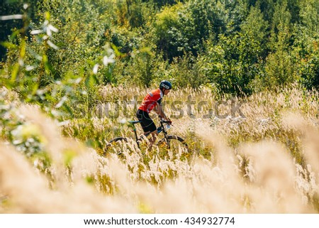 Gomel, Belarus - August 9, 2015: Mountain Bike cyclist riding track in meadow with tall dry  grass at sunny day. Healthy lifestyle active athlete doing sport. Meadow with - stock photo