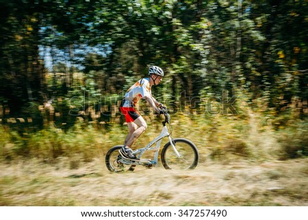 Gomel, Belarus - August 9, 2015: Stepper Bike cyclist riding in forest at sunny day, healthy lifestyle active athlete doing sport. - stock photo
