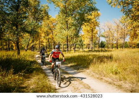 Gomel, Belarus - August 9, 2015: Two mountain bike cyclists riding track at sunny day, healthy lifestyle active athlete doing sport.