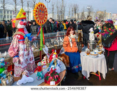 GOMEL, BELARUS - FEBRUARY 21, 2015: Traditional celebration of Shrovetide. Unidentified people walk near Exhibition Shrovetide dolls and pigeons