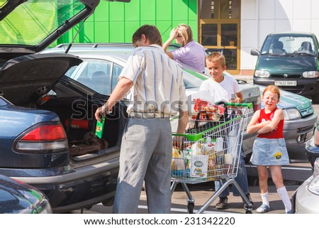 GOMEL, BELARUS - JULY 10, 2010: Unidentified man take out goods from shopping cart to back of the car in the parking. - stock photo