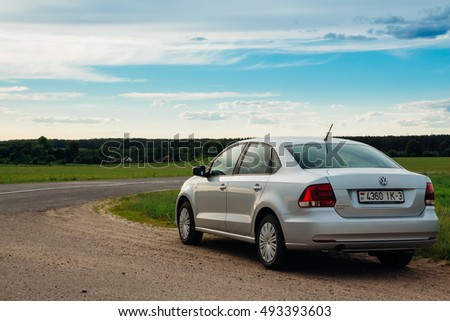 Gomel, Belarus - June 13, 2016: Parked at the side of the road Volkswagen Polo in the countryside in the background the village and the forest