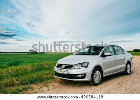 Gomel, Belarus - June 13, 2016: Volkswagen Polo Car Parking On A Roadside Of Country Road On A Background Of Green Spring Fields Or Meadow