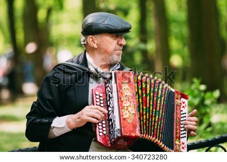 Gomel, Belarus - May 9, 2015: Street Busker performing songs in city park - stock photo