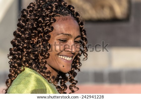 Gonder, Ethiopia - January 19, 2012: Portrait of a young woman with beautiful hair in the street of Gonder during the Timkat holiday, the important Ethiopian Orthodox celebration of Epiphany.