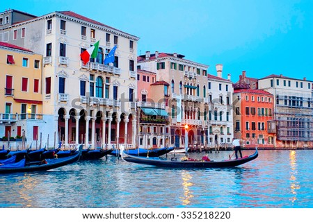 Gondola on a canal in Venice at colorful dusk. Italy - stock photo