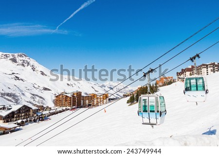 Gondola on the background of the village of Les Menuires. Resort 3 Valleys, French Alps - stock photo