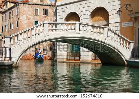 Gondola ride towards bridge in Venice, Italy.  - stock photo