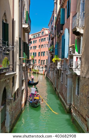 Gondola rides on narrow channel in Venice, Italy
