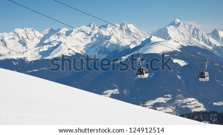 Gondola ski lift and snow covered mountain range in the background. - stock photo