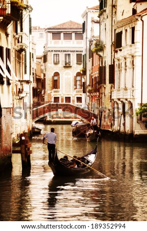 Gondola traveling down the canals of Venice in Italy - stock photo
