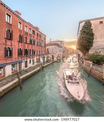 Gondola with gondolier in Venice channel, Italy