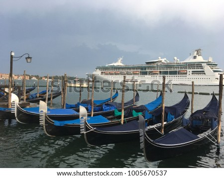Gondolas and a passing cruise ship seen from San Marco Square in Venice, Italy