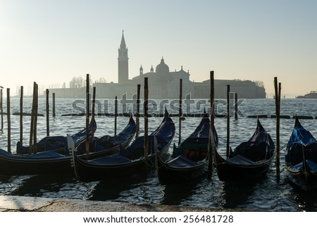 Gondolas and the view of Church of San Giorgio in the morning fog. - stock photo