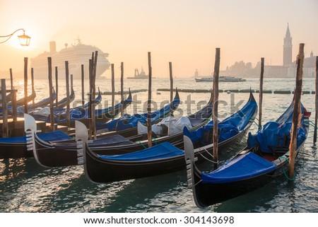 Gondolas at sunrise and a huge cruise ship on the background, Venice, Venezia, Italy, Europe, - stock photo
