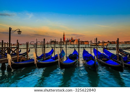 Gondolas in Venice - sunset with San Giorgio Maggiore church. San Marco, Venice, Italy. (filtered, intentional motion blur). - stock photo