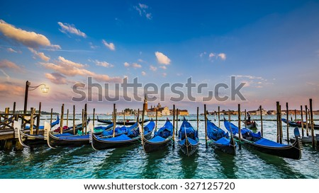 Gondolas in Venice - sunset with San Giorgio Maggiore church. San Marco, Venice, Italy (filtered, intentional motion blur). - stock photo