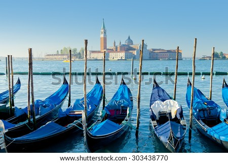 Gondolas moored by Saint Mark square with San Giorgio di Maggior - stock photo