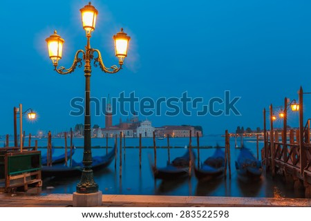 Gondolas moored by Saint Mark square with San Giorgio di Maggiore church in the background at twilight in Venice lagoon, Italia - stock photo