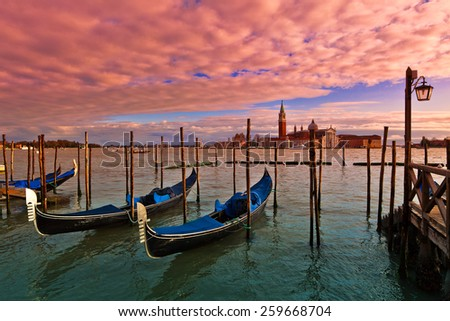Gondolas on Grand Canal and San Giorgio Maggiore church on background at sunset time in Venice, Italy. - stock photo