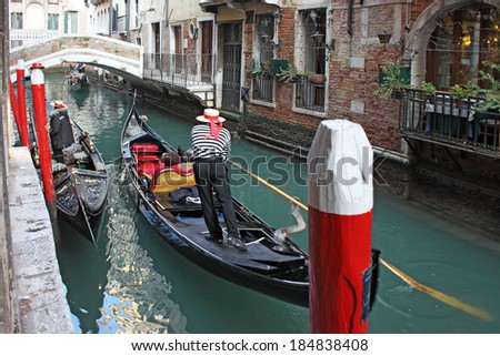 Gondolas transporting tourists in one of the many canals of Venice - stock photo