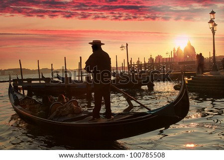 Gondolier against beautiful sunset in Venice, Italy - stock photo
