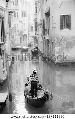 Gondolier guiding a gondola in narrow Venetian canal - stock photo
