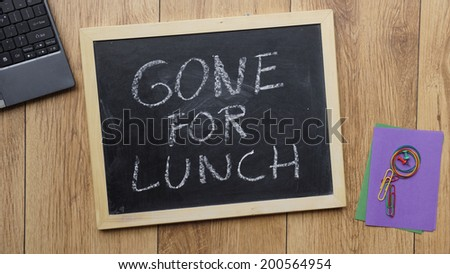 Gone for lunch written on a chalkboard at the office - stock photo