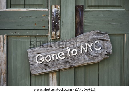 Gone to New York City sign on old green door. - stock photo