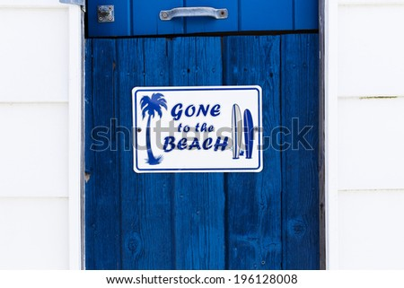 Gone to the Beach Sign on a Blue Painted Wood Door - stock photo