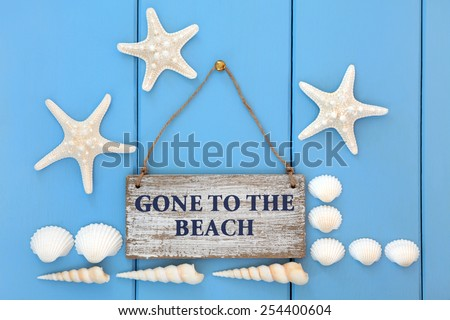 Gone to the beach sign with starfish, cockle and turritella seashells over wooden blue background. - stock photo