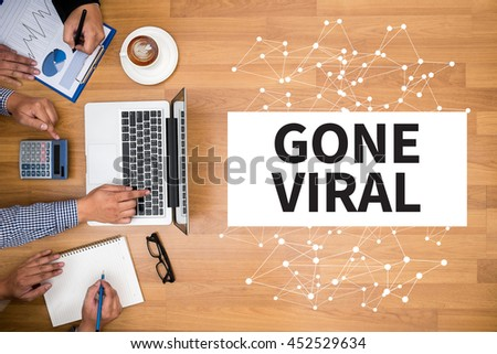 GONE VIRAL Business team hands at work with financial reports and a laptop - stock photo