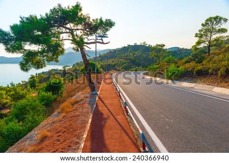 good asphalt road in the mountains near the sea - stock photo