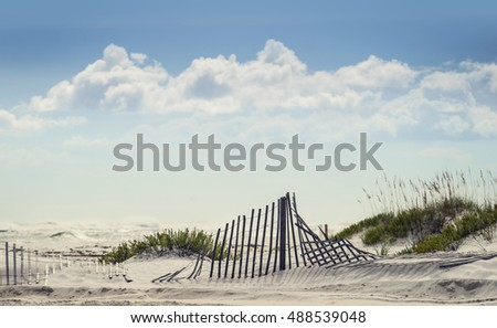 Good background shot of puffy clouds and blue sky with sand fence in the dunes on a sunny day at Florida Beach.