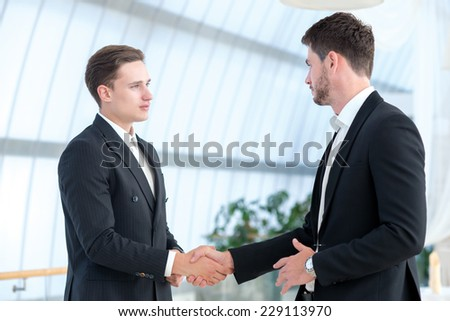 Good business deal. Two successful business partners are shaking hands and looking at each other with confidence
