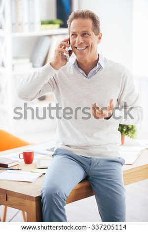 Good business talk. Cheerful mature man talking on the mobile phone and smiling while leaning at the desk in office - stock photo