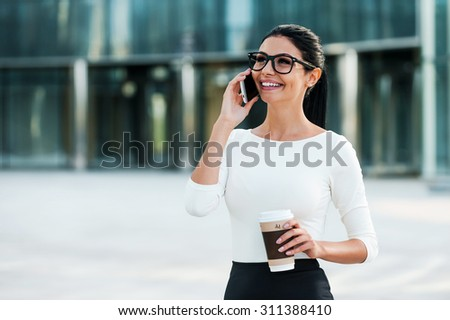 Good business talk. Cheerful young businesswoman talking on the mobile phone and holding cup of coffee while standing outdoors - stock photo