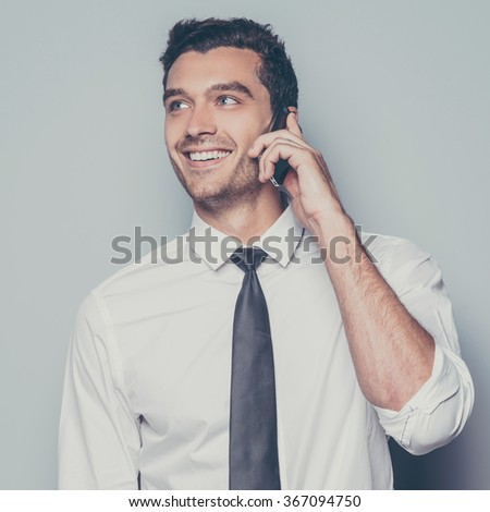 Good business talk. Cheerful young man talking on the mobile phone and smiling while standing against grey background - stock photo