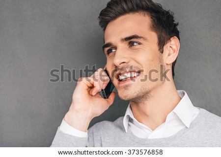 Good business talk. Close-up of cheerful young man talking on the mobile phone and smiling while standing against grey background - stock photo