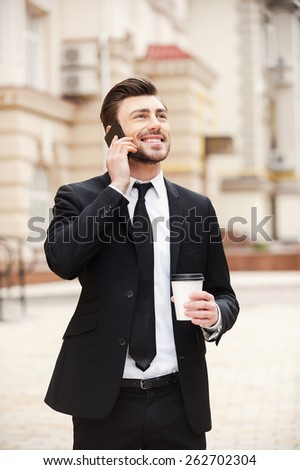 Good business talk. Handsome young man in formalwear talking on the mobile phone and smiling while standing outdoors - stock photo