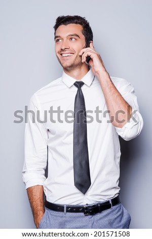 Good business talk. Handsome young man in shirt and tie talking on the mobile phone and smiling while standing against grey background  - stock photo