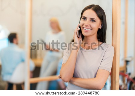 Good business talk. Happy young woman talking on the mobile phone and smiling while her colleagues working in the background - stock photo
