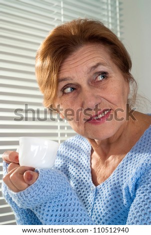 Good Caucasian aged woman sitting on a light background