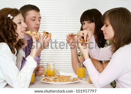 Good Caucasian charming company of four people sit and eat pizza at a cafe