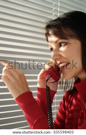 Good Caucasian woman sitting with a phone on a light background