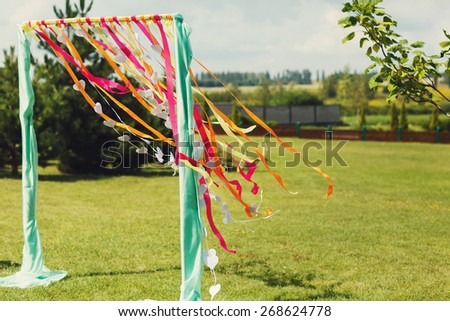 good color wedding arch on a background of green grass and sky - stock photo