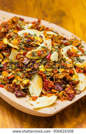 Good cuisine. Closeup colored spices for pasta mix on wooden spoon