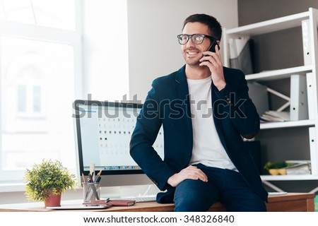 Good day for big deals. Handsome young man talking on the mobile phone and smiling while leaning at the desk in office - stock photo