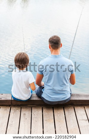 Good day for fishing. Rear view of father and son fishing while sitting on quayside together - stock photo